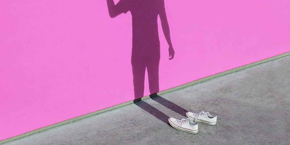 Trainers with no body but a shadow on pink wall