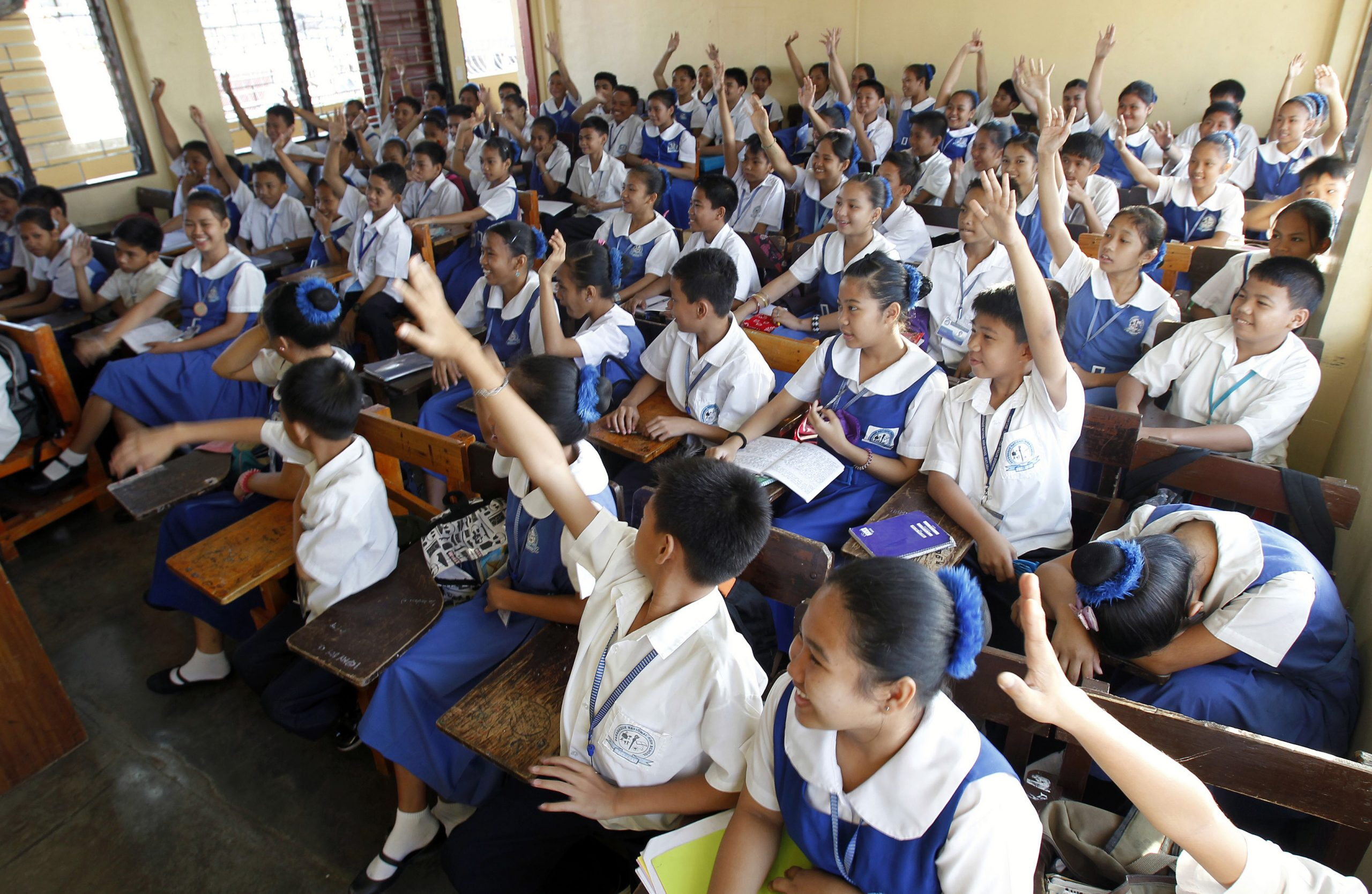 Students raise their hands to answer questions in a classroom at a public high school in Paranaque city