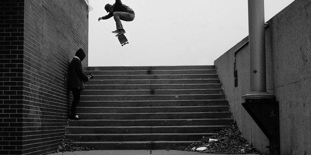 Skateboarder doing trick over steps