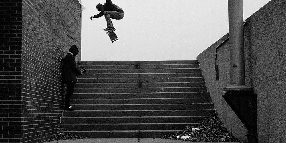 Skateboarder doing trick over steps