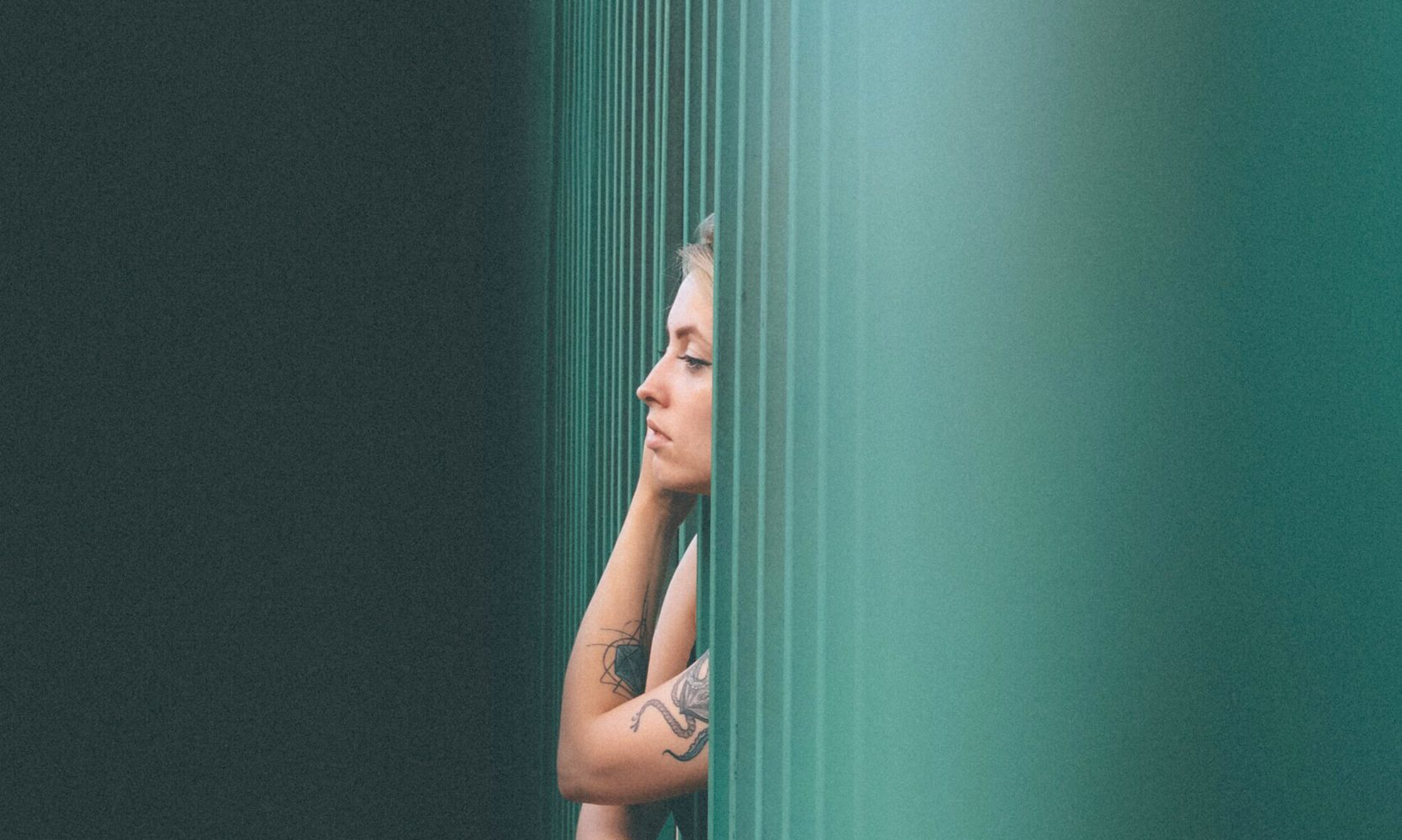 girl with tattoos green hues